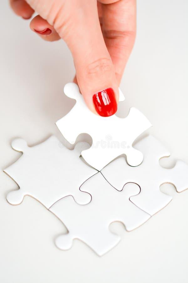 Kobiety ręka dostosowywa prawego kawałek łamigłówki proponowania networking biznesowy pojęcie zdjęcie stock