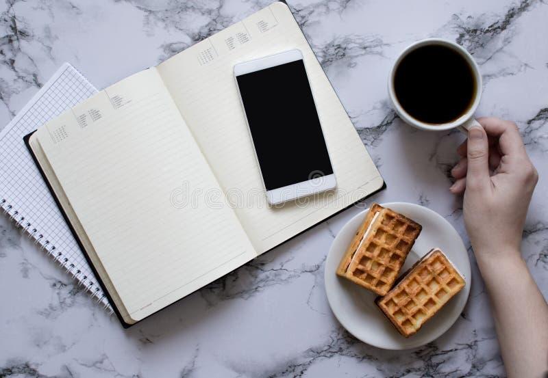 Kobiety ręka, filiżanka kawy, planistyczny dzień, biznesowy lunch i smartphone, fotografia royalty free