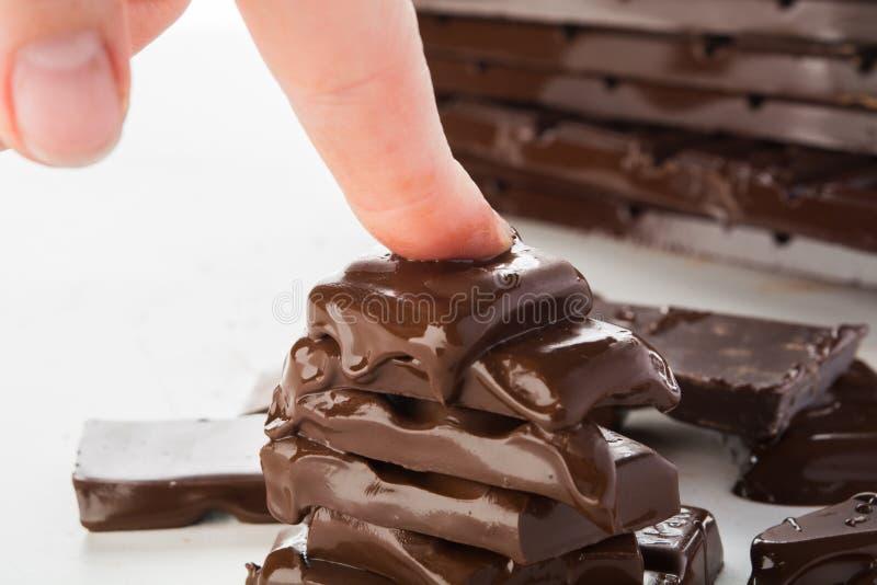 Kobiety ręka jest naciskowym stapiania stertą czekolada, nienawiści czekolady pojęcie zdjęcia royalty free