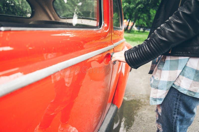 Kobiety ręka otwiera drzwi stary retro samochód obraz stock