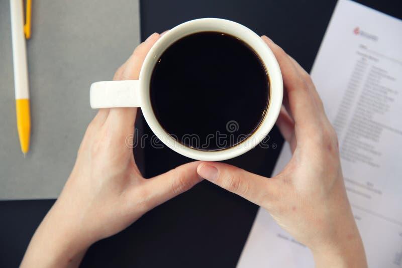 Kobiety ręka pije kawę z biznesowym papierem zdjęcia stock