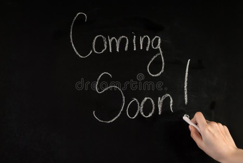 Kobiety ręka pisze słowie Przychodzi Wkrótce na blackboard z biel kredą zdjęcia stock