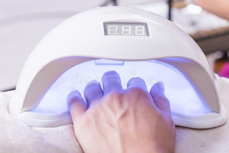 Kobiety ręka podczas gdy proces manicure w gwoździa sklepie Piękny przeciw obrazy stock