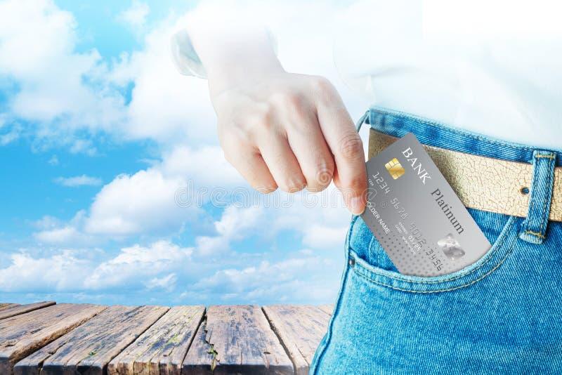 Kobiety ręka - podnosi up realistycznego kredyt lub kartę debetową z starym drewno stołem na obłocznym nieba tle zdjęcie royalty free