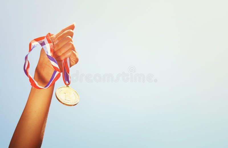 Kobiety ręka podnosząca, trzymający złotego medal przeciw niebu nagrody i zwycięstwa pojęcie fotografia stock