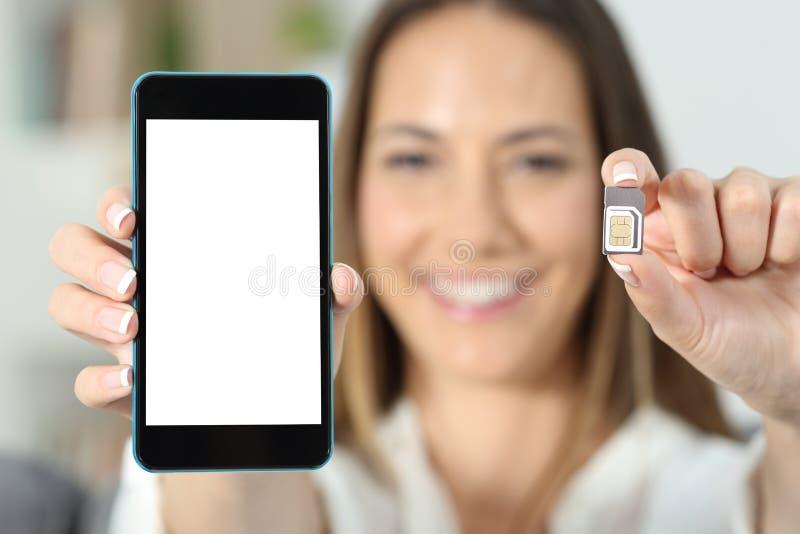 Kobiety ręka pokazuje sim kartę i mądrze telefon zdjęcie royalty free