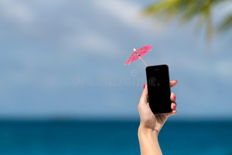 Kobiety ręka pokazuje telefonu komórkowego i koktajlu parasol na niebie fotografia stock