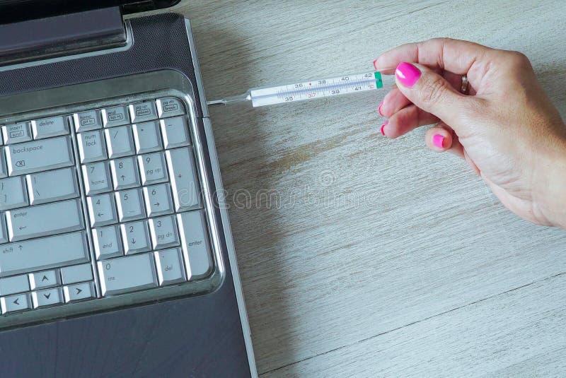 Kobiety ręka PRZEDSTAWIA termometr NA komputerze zdjęcie royalty free