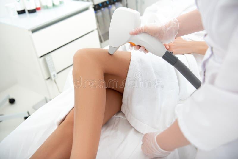Kobiety ręka robi włosianemu usunięciu z urządzeniem zdjęcia stock
