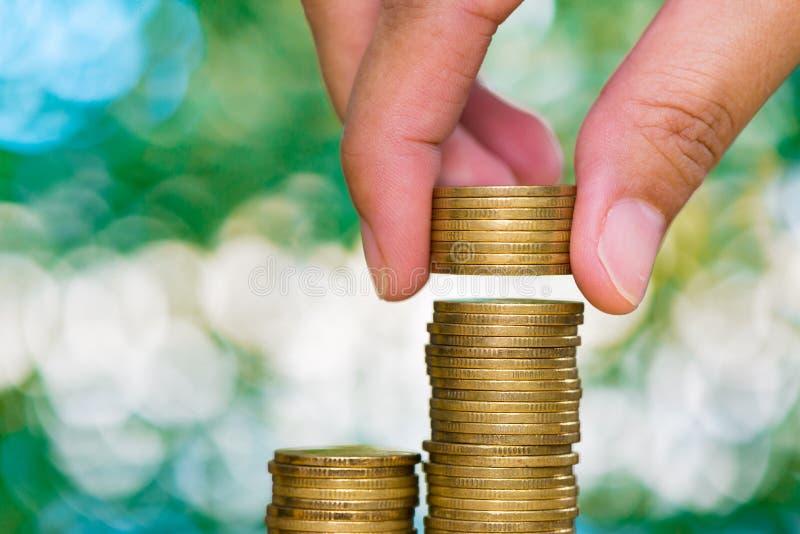 Kobiety ręka stawia monetę na kroku monet sterty i złocistej monety pieniądze zdjęcie stock