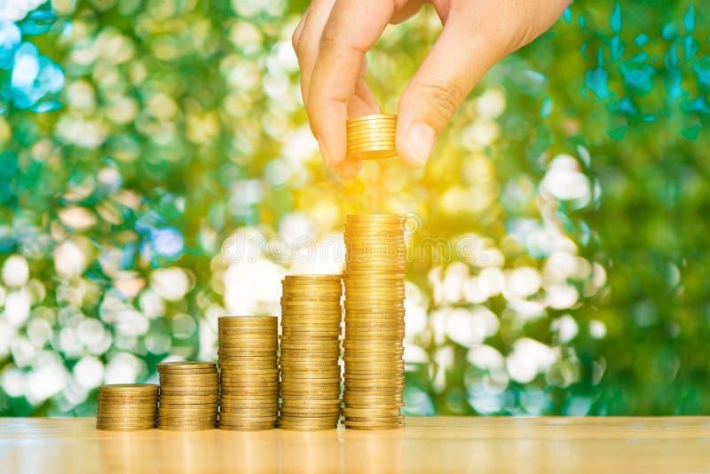 Kobiety ręka stawia monetę na kroku monet sterty i złocistej monety pieniądze obrazy royalty free