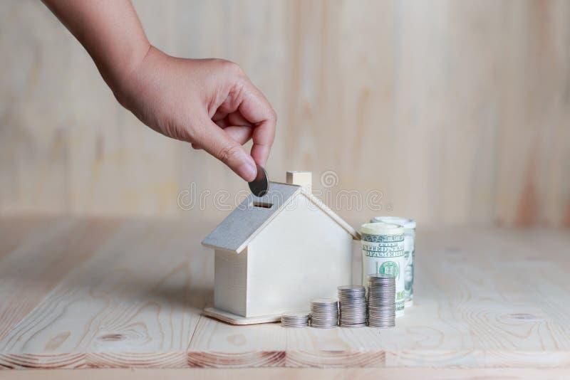 Kobiety ręka stawia monetę wewnątrz drewniany domowy prosiątko banka financ zdjęcie stock