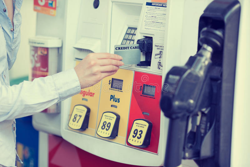 Kobiety ręka swiping kredytową kartę przy benzynową stacją pomp obrazy royalty free
