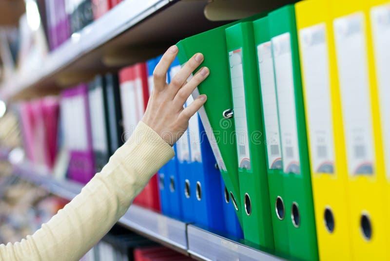 Dziewczyny ręka bierze dużą falcówkę od półek z biurowymi kartotekami. obraz royalty free