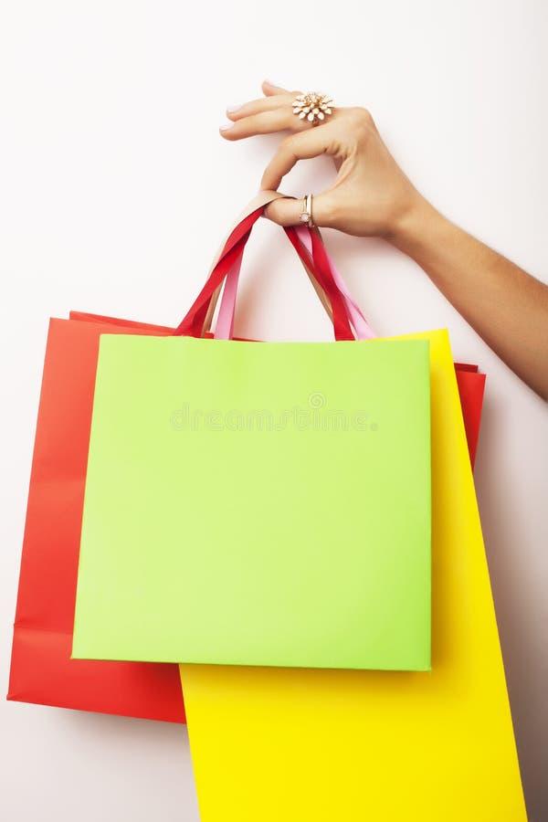Kobiety ręka trzyma few papierowe torby na białym tle, robi zakupy sprzedaży pojęcie obrazy stock