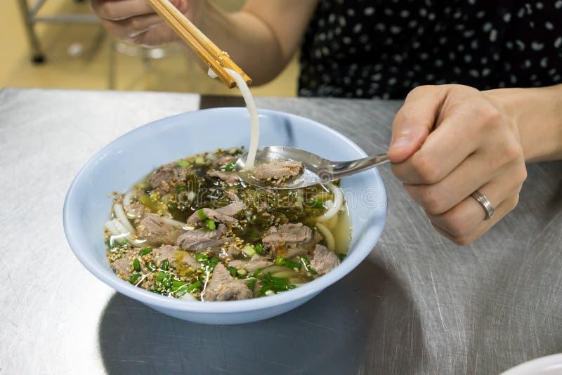 Kobiety ręka trzyma Hainan ryżowego kluski z chopsticks nad b zdjęcie royalty free