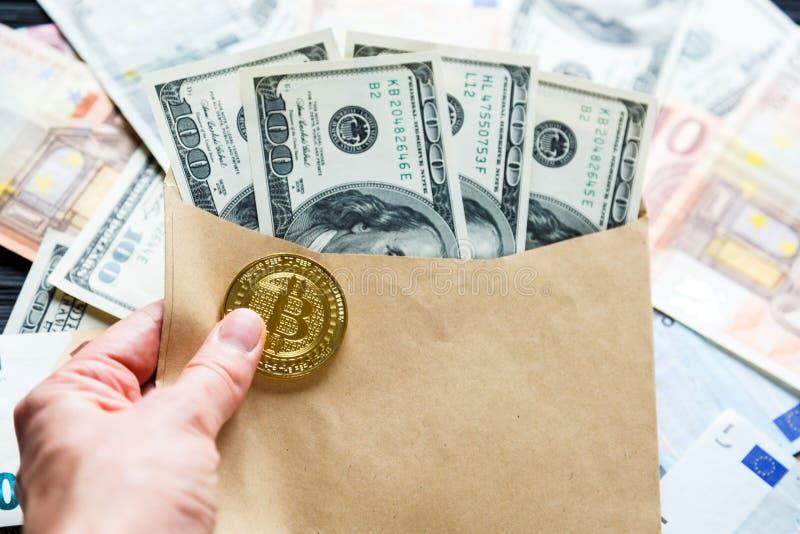 Kobiety ręka trzyma kopertę z dolarami i bitcoin Inwestycja, ryzyko, pensja, oszczędzania zdjęcie royalty free