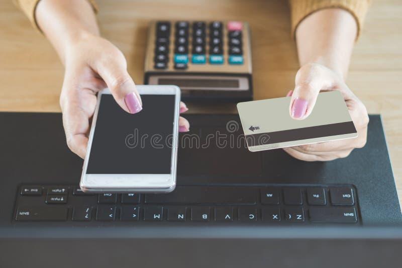 Kobiety ręka trzyma mądrze telefon i karta kredytowa robi online zapłacie z komputerowym laptopem obrazy royalty free