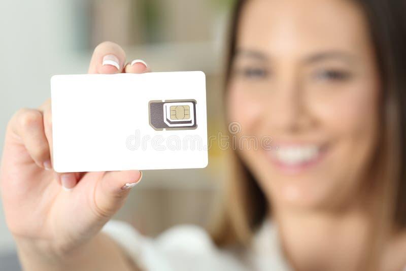 Kobiety ręka trzyma nową pustą sim kartę zdjęcia stock