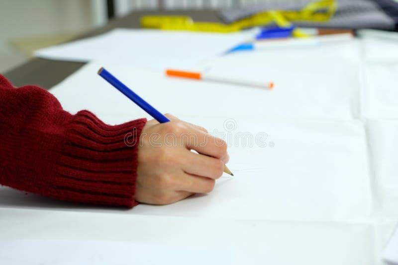 Kobiety ręka trzyma ołówkowego rysunek i skectching kreatywnie projekt sztuki pomysły na białej księdze przy pracującym biurkiem zdjęcie royalty free