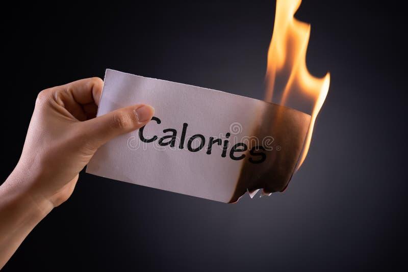 Kobiety ręka trzyma płonącego kawałek papieru z słowo kaloriami by? poj?cia r?k? opieki zdrowotnej pomoc op??nion? pigu?k? fotografia royalty free