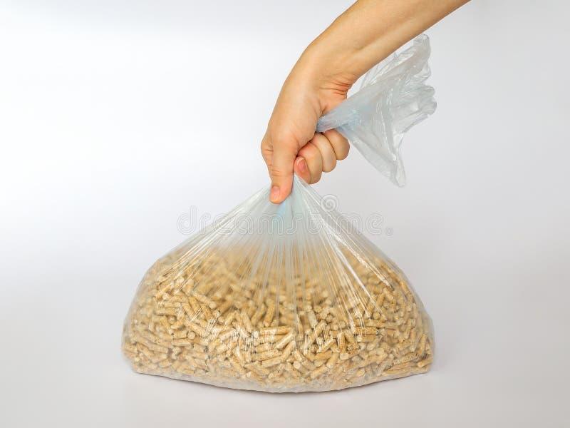 Kobiety ręka trzyma plastikową celofanową torbę z drewnianymi wyrkami na białym tle Alternatywny biopaliwo od trociny dla palić w obraz royalty free