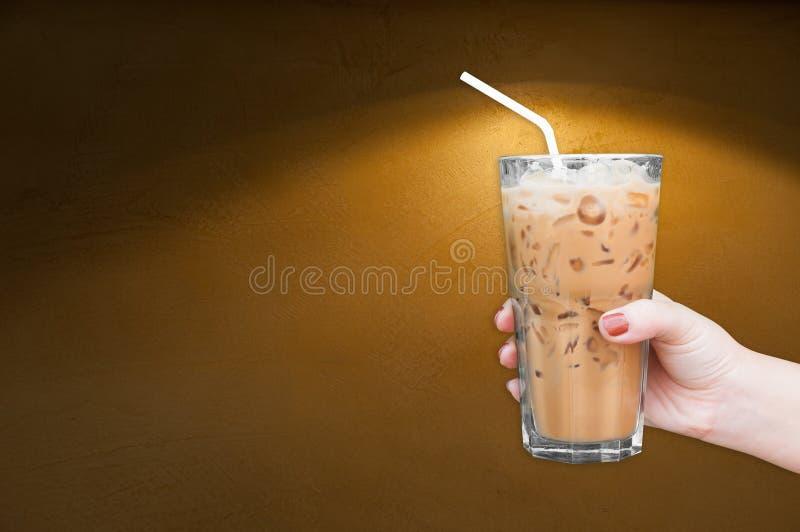 Kobiety ręka trzyma szklaną lukrową kawę na brown grungy ścianie fotografia stock