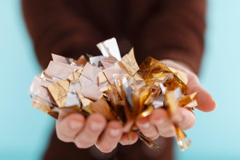 Kobiety ręka trzyma złotych confetti zdjęcie stock
