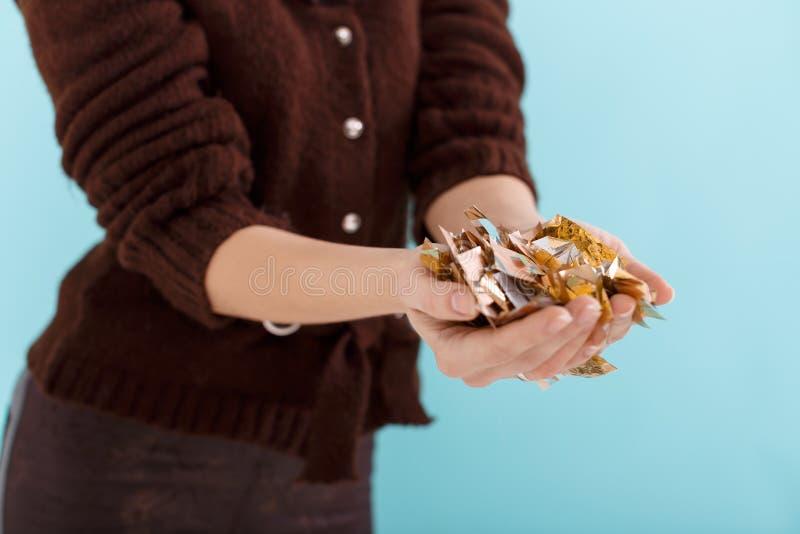 Kobiety ręka trzyma złotych confetti zdjęcia stock