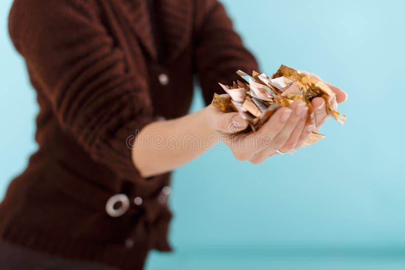 Kobiety ręka trzyma złotych confetti fotografia stock