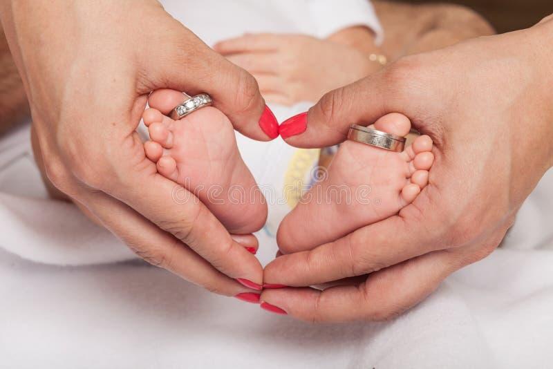 Kobiety ręka tworzy serce wokoło stopy dziecko z obrączkami ślubnymi wychowywa fotografia stock