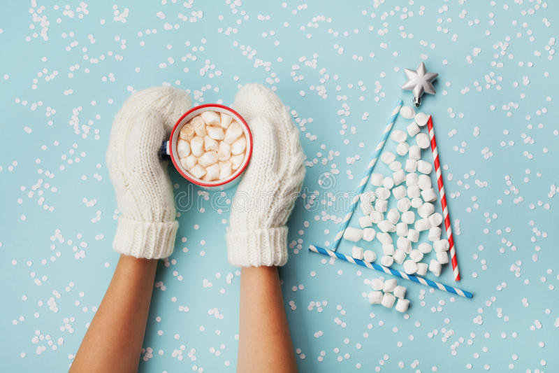 Kobiety ręka w mitynka chwyta filiżance gorący kakao, czekolada lub bożego narodzenia jedlinowy drzewo robić marshmallow dekorują obraz royalty free