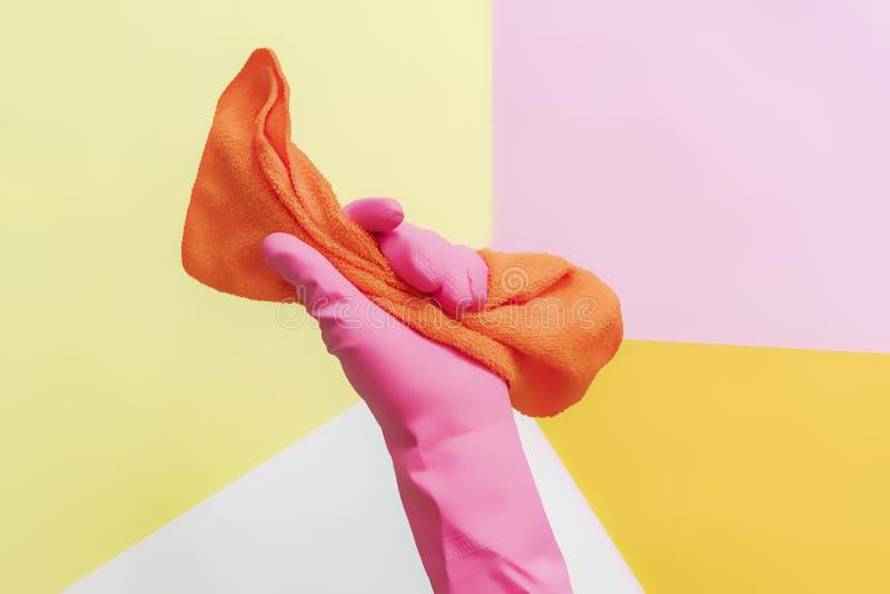 Kobiety ręka w różowych rękawiczkach trzyma gałganianymi przeciw stałego koloru tłu, kreatywnie pojęcie f obrazy stock