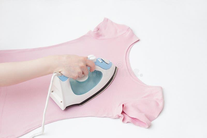 Kobiety ręka z żelaznymi prasowanie menchii ubraniami obrazy stock