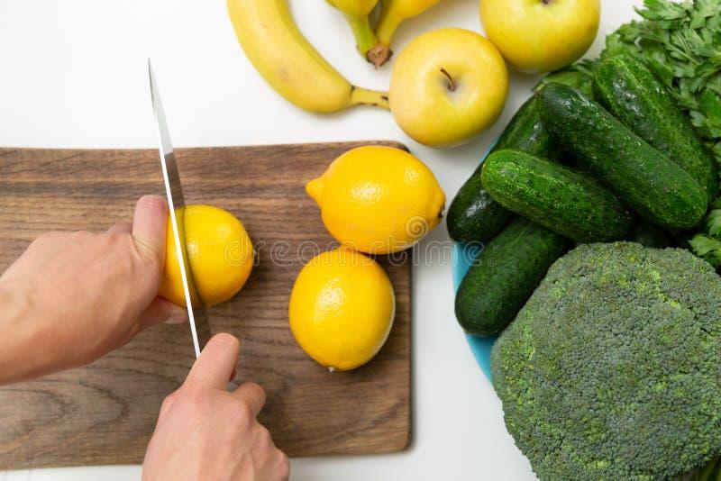 Kobiety ręka z nożową tnącą cytryną na drewnianej desce Zielony Smoothie przygotowanie zdjęcie stock