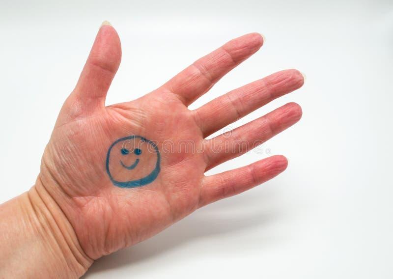 Kobiety ręka z smiley twarzą rysującą w palmie odizolowywającej na bielu obrazy stock
