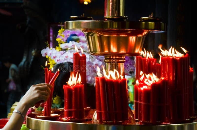 Kobiety ręka zaświeca czerwone świeczki w Buddyjskiej świątyni, Tajwan, Chiny Religijny pojęcie, duchowość, wiara, bóg Buddha, sy obrazy royalty free