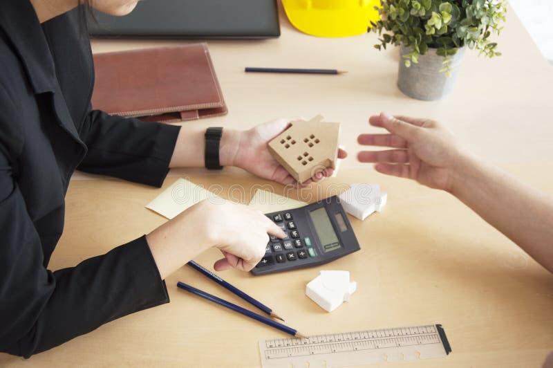 Kobiety ręki chwyt domu model z kalkuluje dla lokalowych pożyczek zdjęcie royalty free