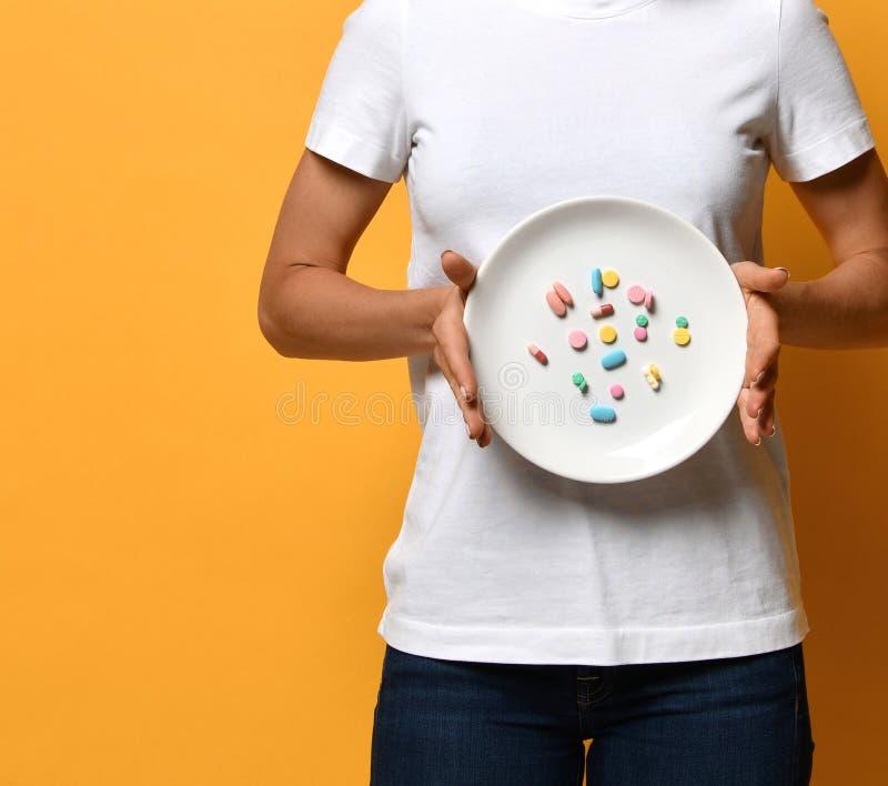 Kobiety ręki chwyta bielu żywiony talerz z różną kolor pastylki pigułek diety nadprogramów ciężaru recepturową stratą narkotyzuje obrazy stock