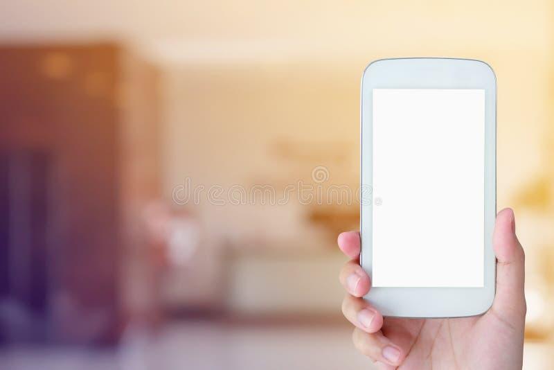 Kobiety ręki chwyta mobilny smartphone z hotelu lobby obrazy royalty free