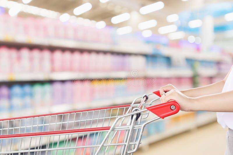 Kobiety ręki chwyta pusty czerwony wózek na zakupy zdjęcie stock