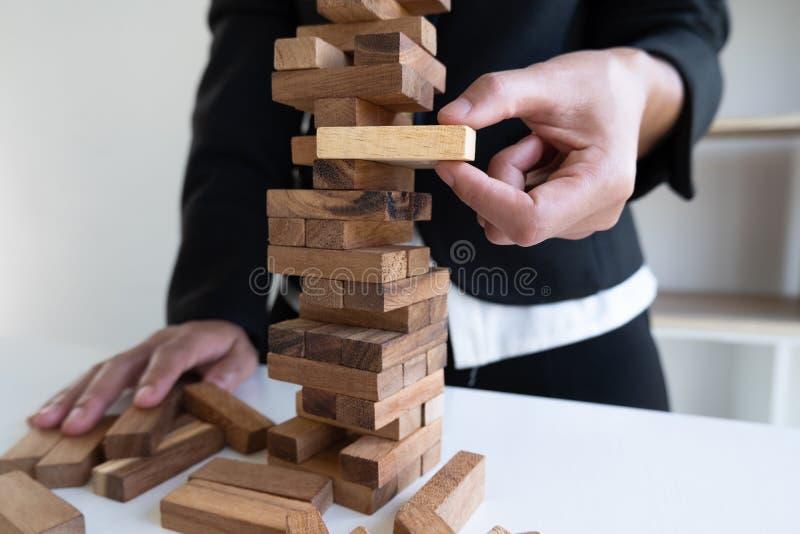 Kobiety ręki ciągnienia bloku drewno ostrożnie, pojęcia ryzyko zarządzanie zdjęcia stock