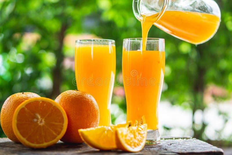 Kobiety ręki dolewania sok pomarańczowy na szkłach z plasterek pomarańcze na drewnianym tle obrazy royalty free