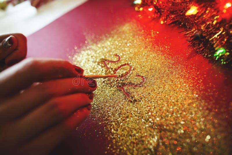 Kobiety ręki farba postać 2020 w claret tle z błyska Nowego roku `s poj?cie zdjęcie royalty free