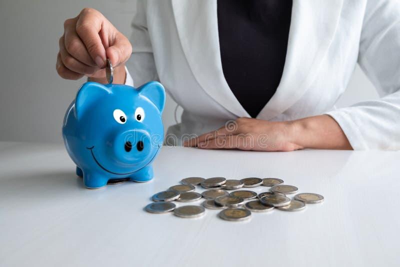 Kobiety ręki kładzenia moneta w błękitnego prosiątko banka oszczędzania pieniądze z monetami wypiętrza zdjęcie stock