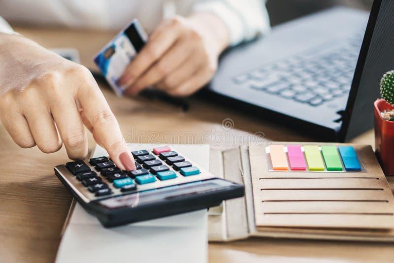 Kobiety ręki kalkulatorscy koszty i dług od kart kredytowych obraz stock