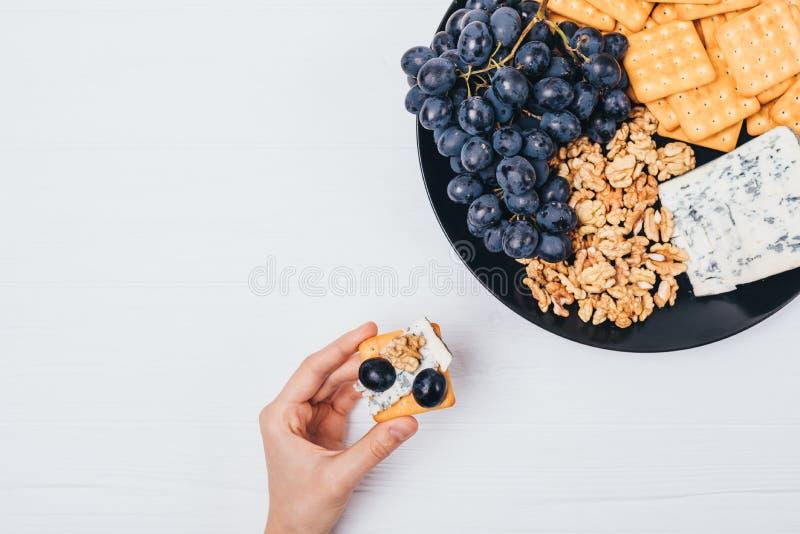 Kobiety ręki mienia canape blisko round talerza z serem, winogronami, krakersami i dokrętkami, odgórny widok Mieszkanie przekąski obraz stock