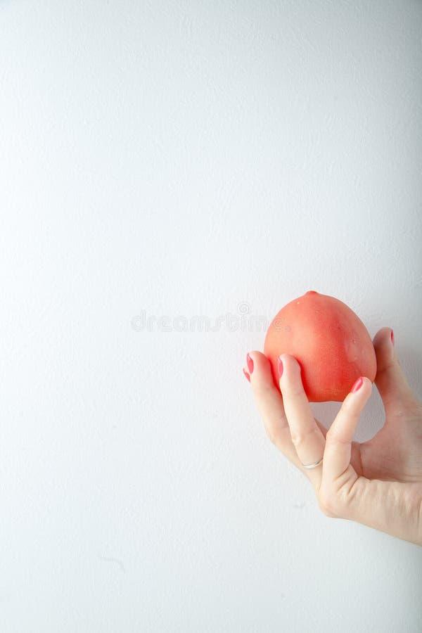 Kobiety ręki mienia czerwony pomidor na białym tle zdjęcie stock