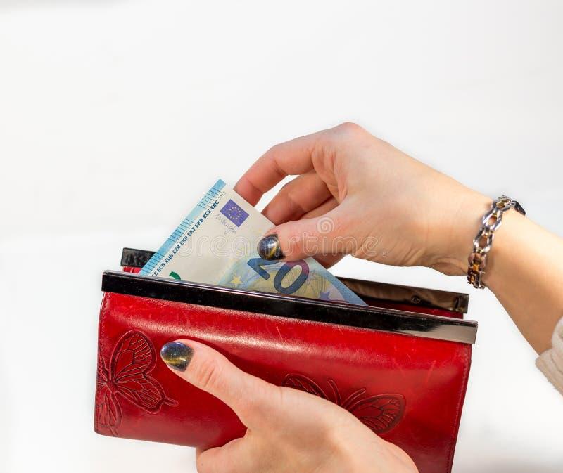 Kobiety ręki mienia czerwony portfel i ciągnąć out pieniądze zdjęcia stock