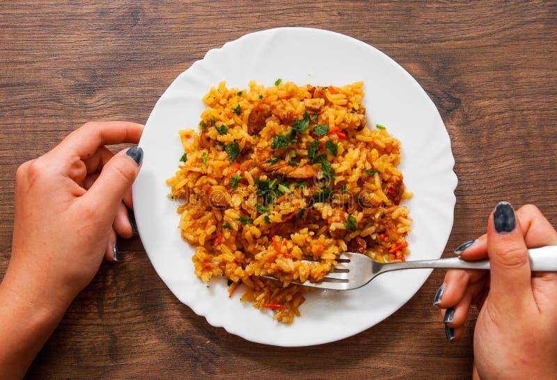 Kobiety ręki mienia rozwidlenie z Rice z warzywami i mięsem w talerzu na drewnianym stole obraz stock